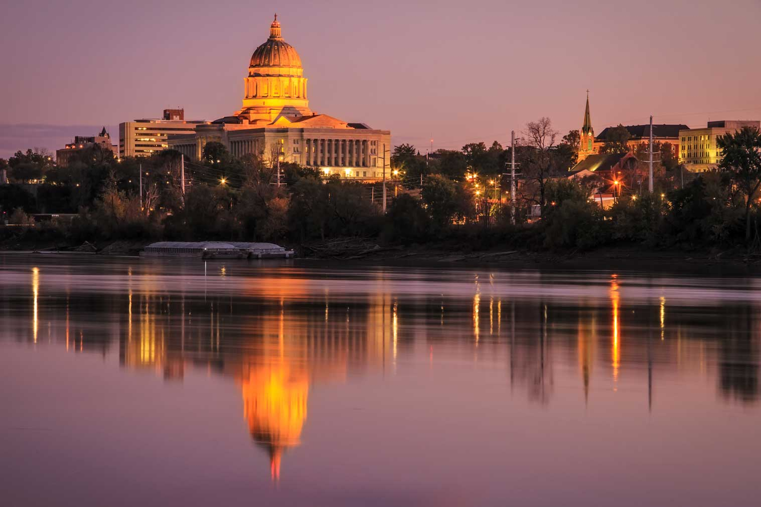 Cityscape Of The Jefferson City Skyline With The Missouri State Capitol Reflecting In The River At Twilight